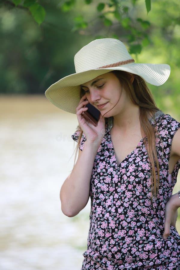 Giovane e donna graziosa che sta chiamando con il suo smartphone fotografie stock libere da diritti