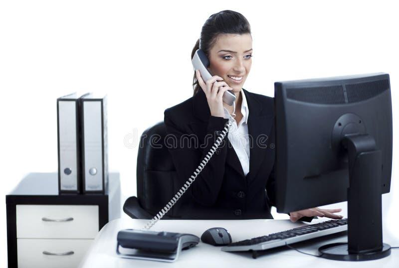 Giovane e donna graziosa di affari che comunica sopra il telefono fotografia stock