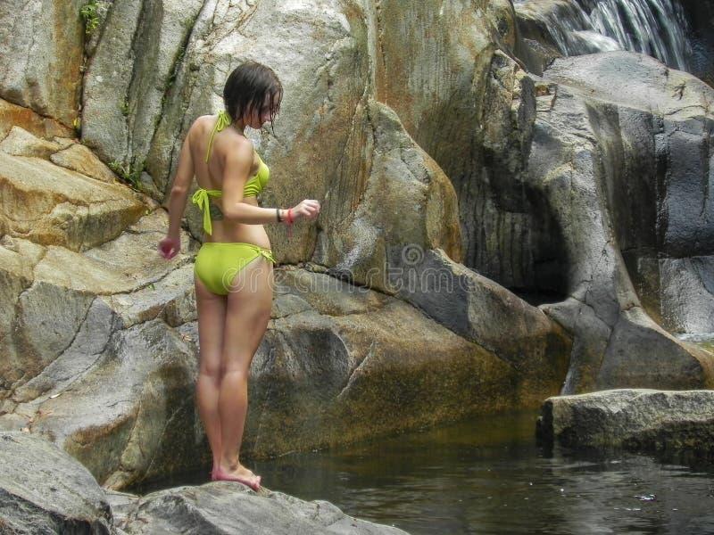 Giovane e donna sexy in un costume da bagno verde su una bella cascata fotografia stock