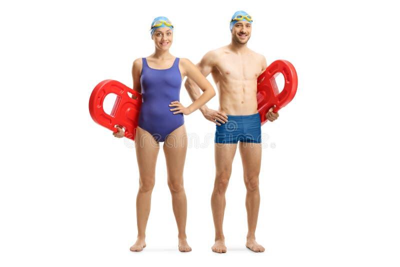 Giovane e donna in vestito di nuoto che tiene i galleggianti di nuoto immagine stock libera da diritti