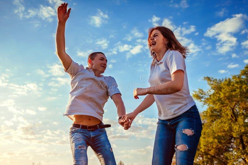 Giovane e funzionamento e salto della donna Coppie divertendosi nel giacimento di primavera al tramonto Risata dei tipi fotografia stock