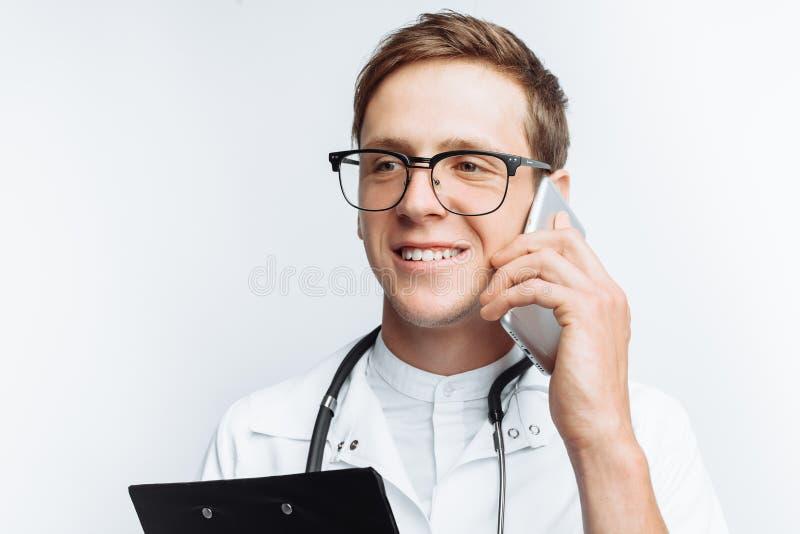 Giovane e medico bello che parla sul telefono con i pazienti, studente dell'interno con la cartella a disposizione, fondo bianco, fotografia stock libera da diritti