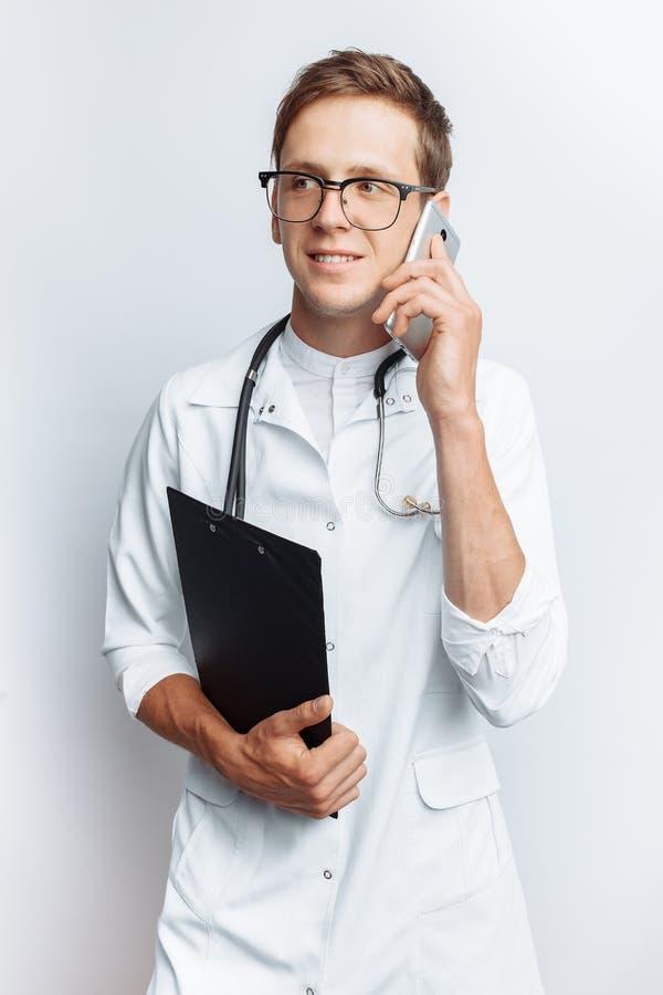Giovane e medico bello che parla sul telefono con i pazienti, studente dell'interno con la cartella a disposizione, fondo bianco, immagine stock libera da diritti