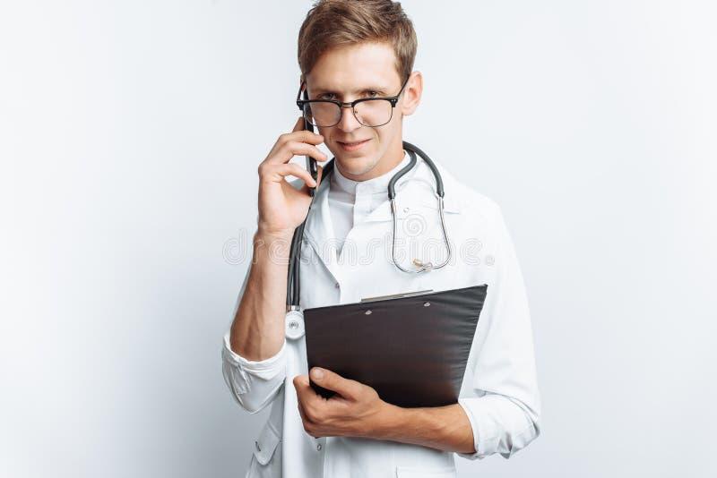 Giovane e medico bello che parla sul telefono con i pazienti, studente dell'interno con la cartella a disposizione, fondo bianco, immagini stock libere da diritti