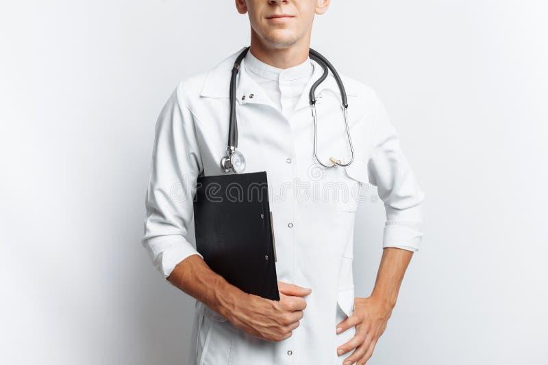 Giovane e medico bello, studente dell'interno con la cartella a disposizione, fondo bianco, per la pubblicità e l'inserzione immagine stock