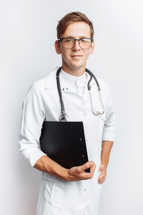 Giovane e medico bello, studente dell'interno con la cartella a disposizione, fondo bianco, per la pubblicità e l'inserzione fotografia stock