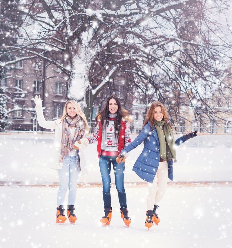 Giovane e ragazza graziosa che pattina sulla pista di pattinaggio sul ghiaccio all'aperto dell'aria aperta ai wi fotografie stock libere da diritti