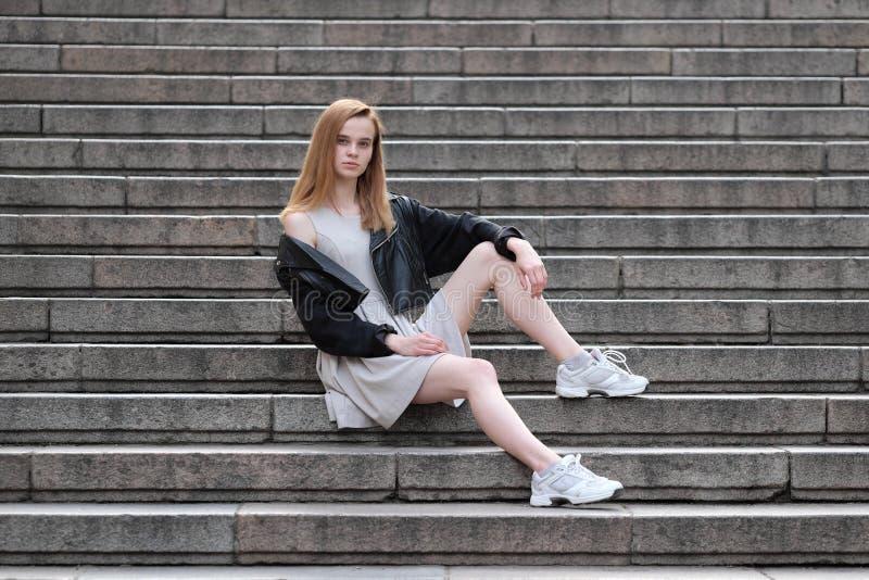 Giovane e ragazza redheaded sexy che posa all'aperto in bomber ed abito fotografia stock libera da diritti