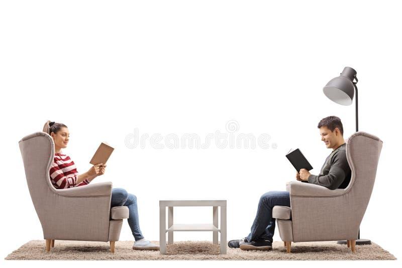 Giovane e una giovane donna messa in libri di lettura delle poltrone fotografie stock