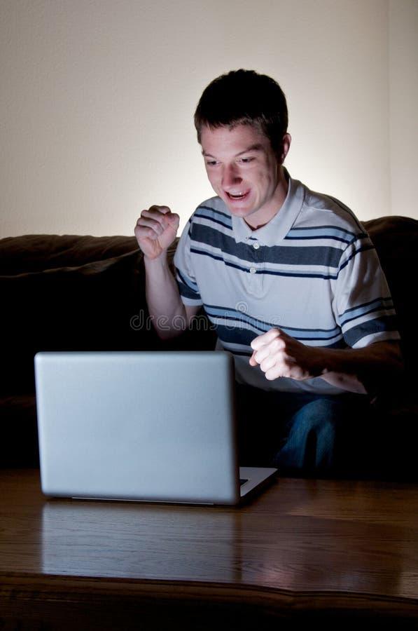 Giovane eccitato dalle notizie sul suo computer immagine stock