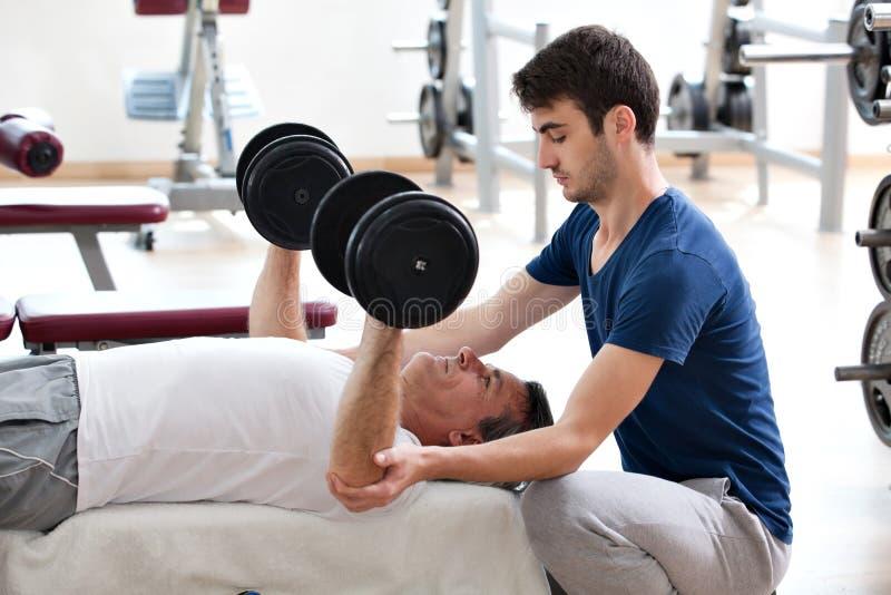 Giovane ed il suo padre in ginnastica immagine stock libera da diritti