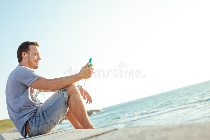 Giovane ed uomo bello con lo smartphone mobile fotografia stock libera da diritti