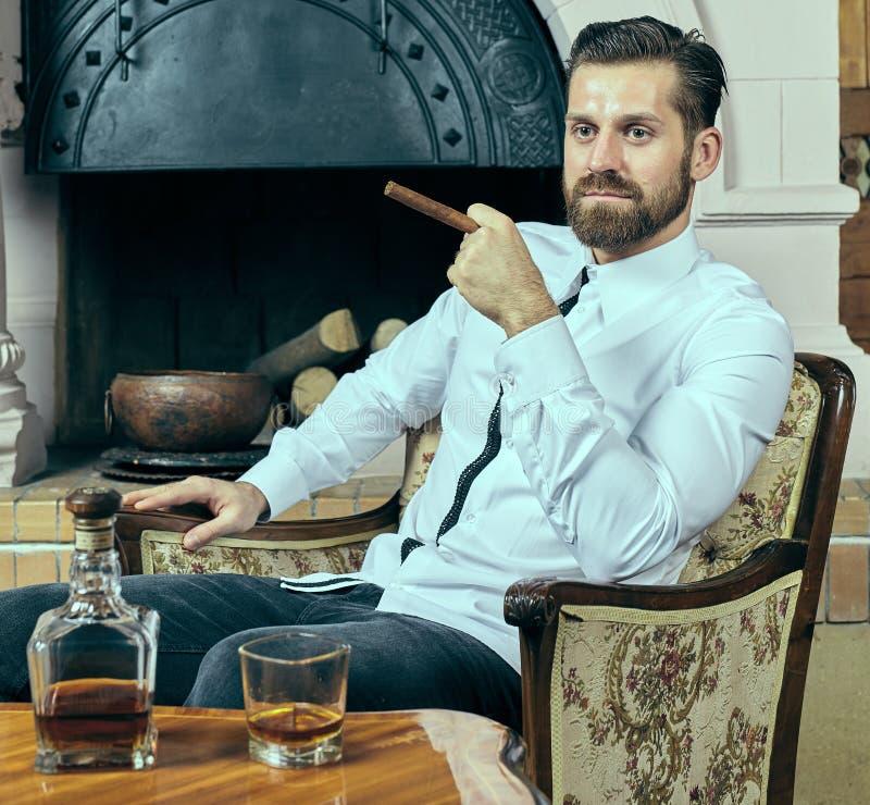 Giovane elegante con whiskey ed il sigaro fotografia stock