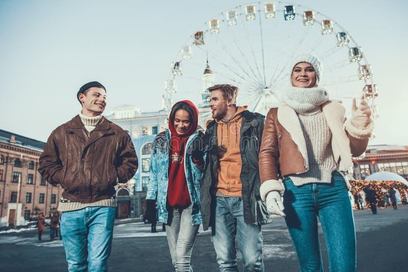 Giovane emozionale che parla con amici mentre camminando con loro fotografie stock libere da diritti