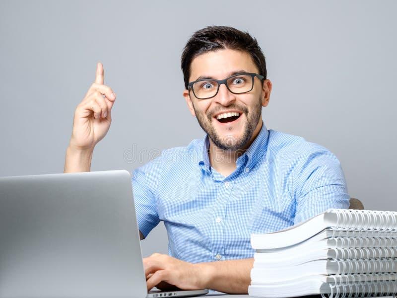 Giovane emozionante con il computer portatile che indica dito su fotografia stock