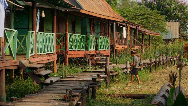 Giovane erbaccia di taglio del giardiniere con il decespugliatore davanti ai bungalow di legno di festa fotografia stock
