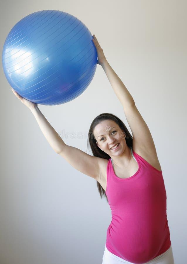 Giovane esercitazione sorridente della donna incinta fotografie stock libere da diritti