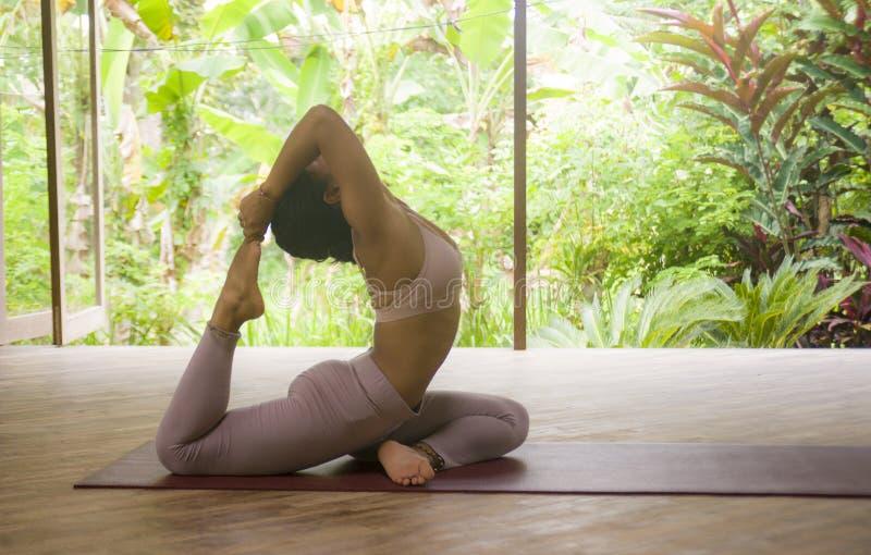 Giovane esercizio di pratica di yoga di acro della donna indonesiana asiatica attraente ed in buona salute dell'acrobata nella po fotografia stock libera da diritti
