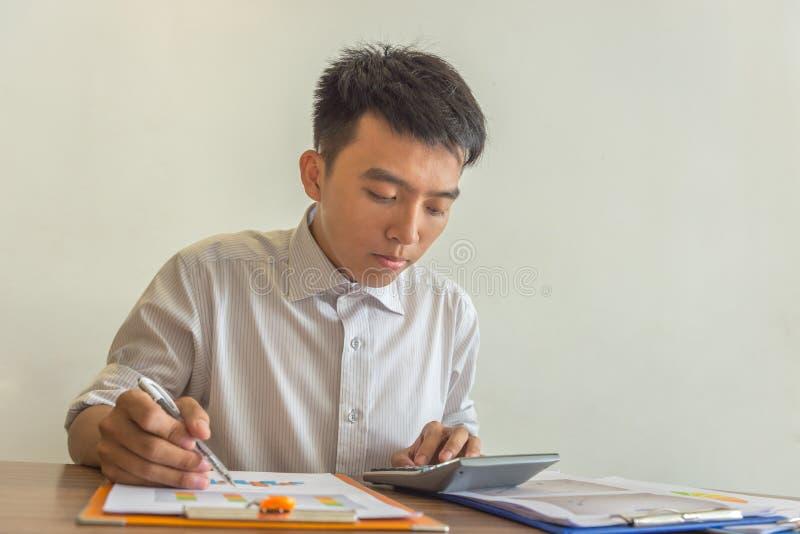 Giovane facendo uso del rapporto finanziario della lettura e del calcolatore fotografia stock