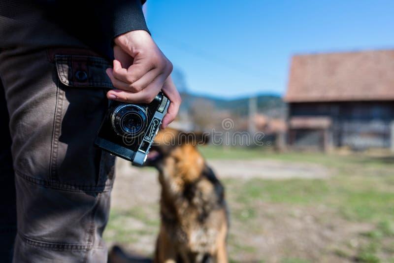 Giovane facendo uso della macchina fotografica russa d'annata, pastore tedesco di seduta davanti lui immagini stock