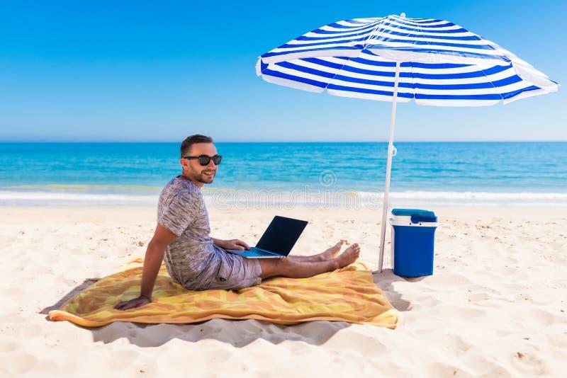Giovane facendo uso di un computer portatile sulla spiaggia sotto l'ombrello Concetti indipendenti fotografia stock libera da diritti