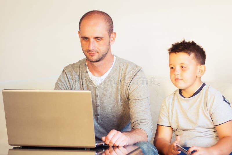 Giovane faher con il bambino che compra online a casa immagini stock libere da diritti