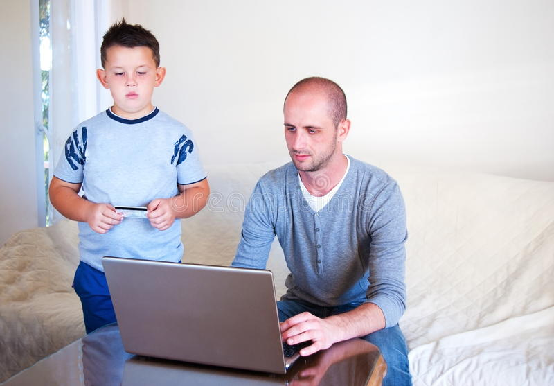 Giovane faher con il bambino che compra online a casa fotografia stock libera da diritti