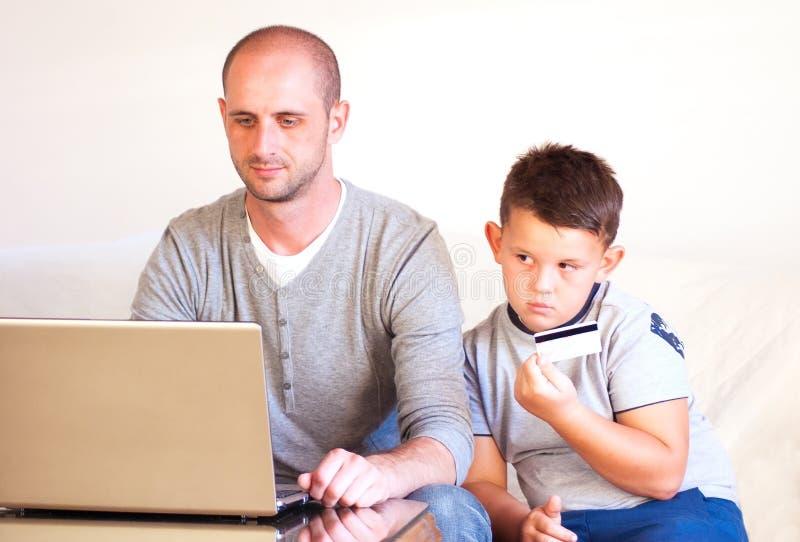 Giovane faher con il bambino che compra online a casa fotografia stock