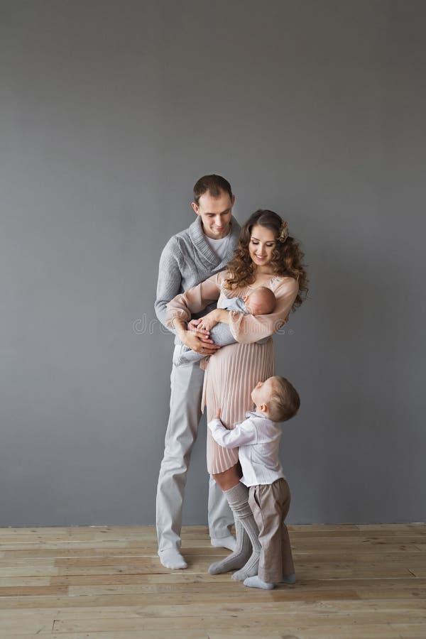 Giovane famiglia adulta con un infante e un bambino in uno studio fotografie stock libere da diritti