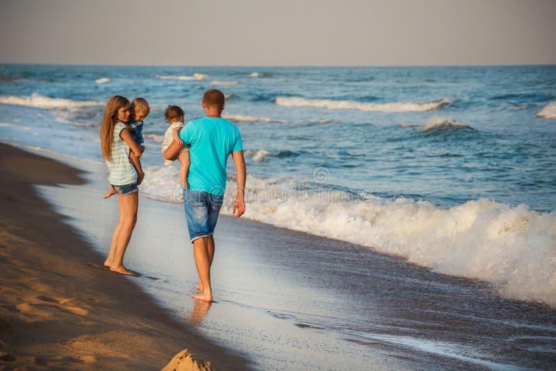 Giovane famiglia amorosa felice con i piccoli bambini che camminano insieme alla spiaggia vicino all'oceano, concetto 'nucleo fam fotografie stock