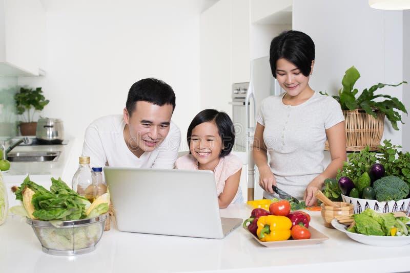 Giovane famiglia asiatica facendo uso del computer insieme a casa immagine stock