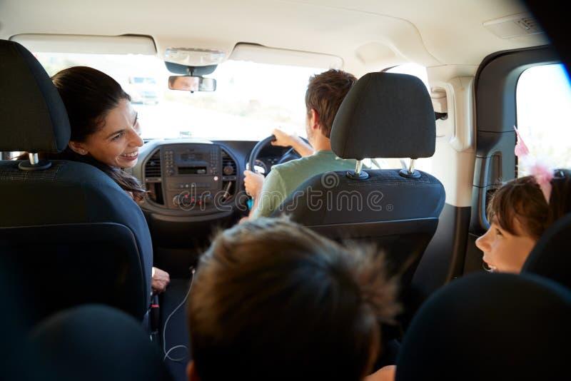 Giovane famiglia bianca che compone un viaggio in loro automobile, fine, colpo interno dell'automobile posteriore di vista immagine stock libera da diritti