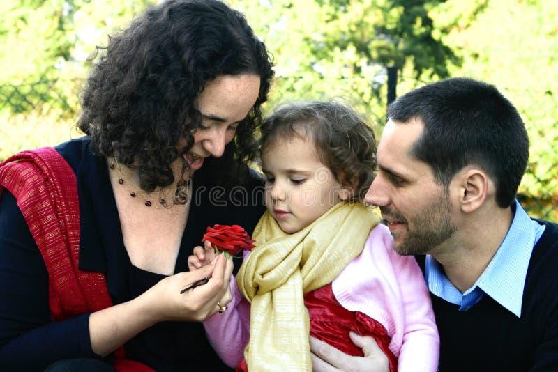 Giovane famiglia che ammira una rosa fotografie stock