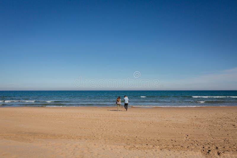 Giovane famiglia che cammina in spiaggia vuota Gandia, Spagna immagine stock libera da diritti