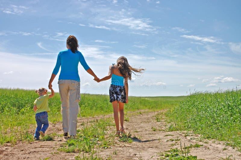 Giovane famiglia che funziona sopra un campo del coltivatore immagine stock