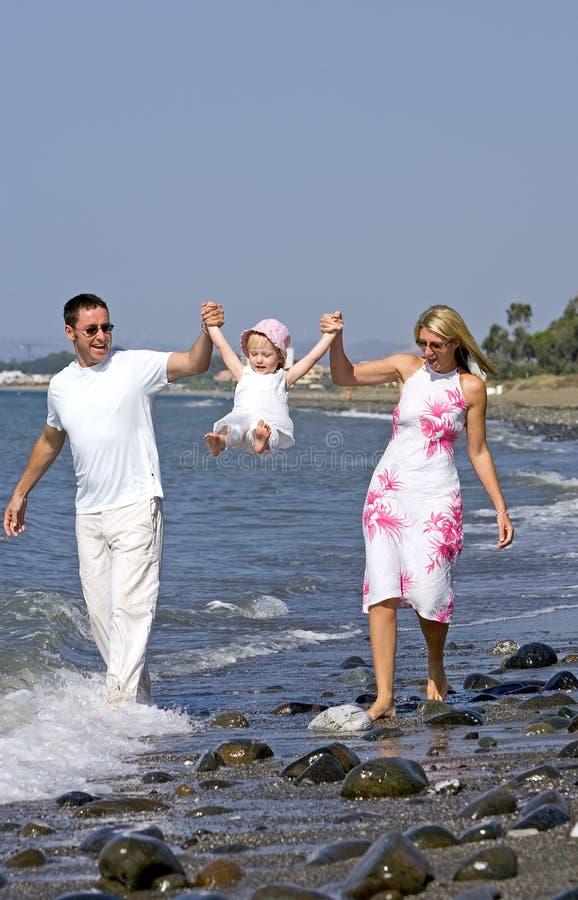 Giovane famiglia che gioca con la figlia sulla spiaggia in Spagna immagine stock libera da diritti