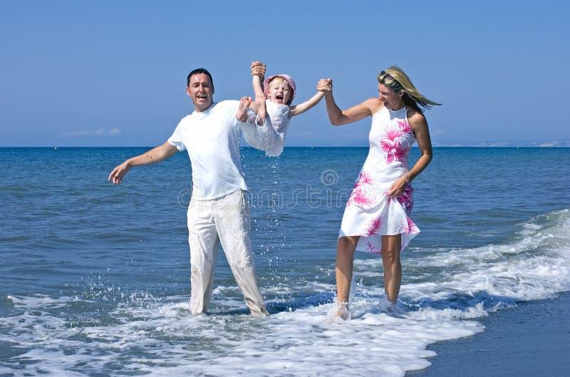 Giovane famiglia che gioca con la figlia sulla spiaggia in Spagna immagine stock