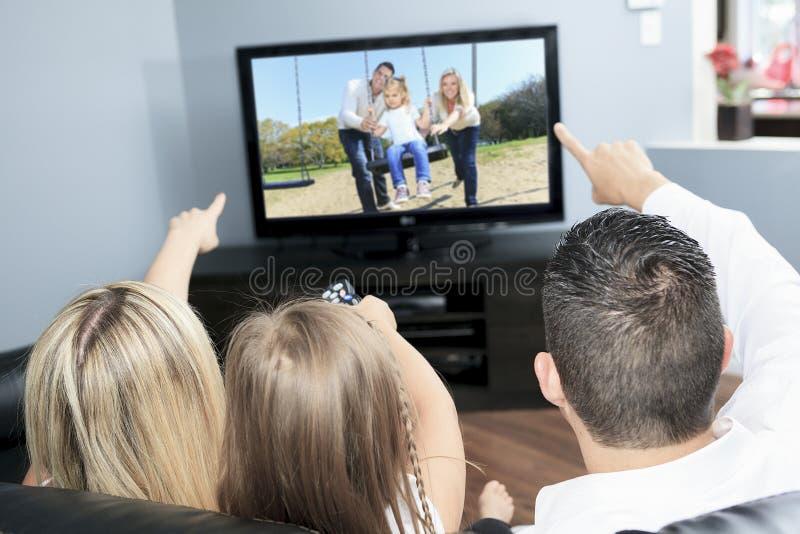 Giovane famiglia che guarda insieme TV a casa fotografia stock libera da diritti