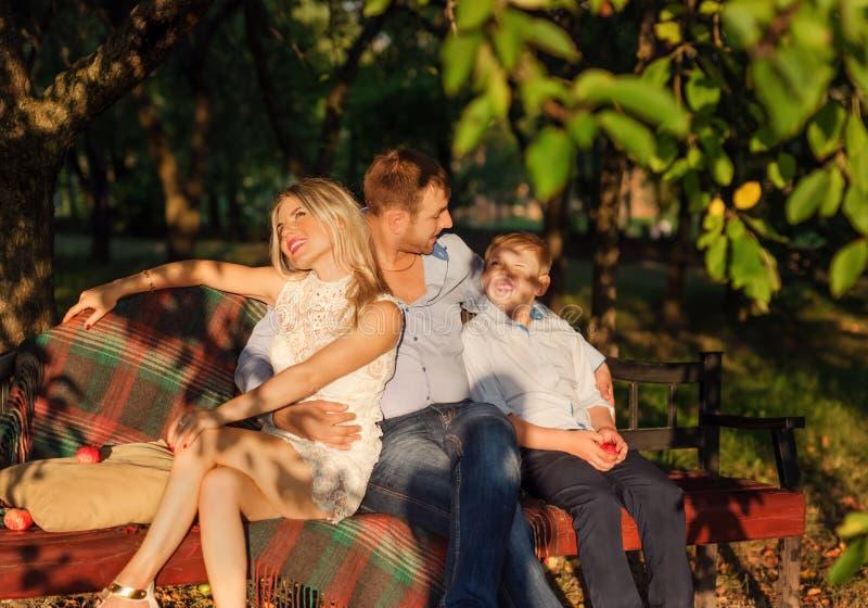Giovane famiglia che si siede sul banco del giardino immagini stock