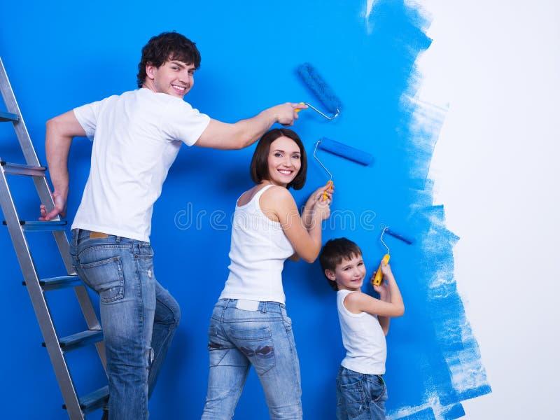 Giovane famiglia che vernicia la parete fotografie stock