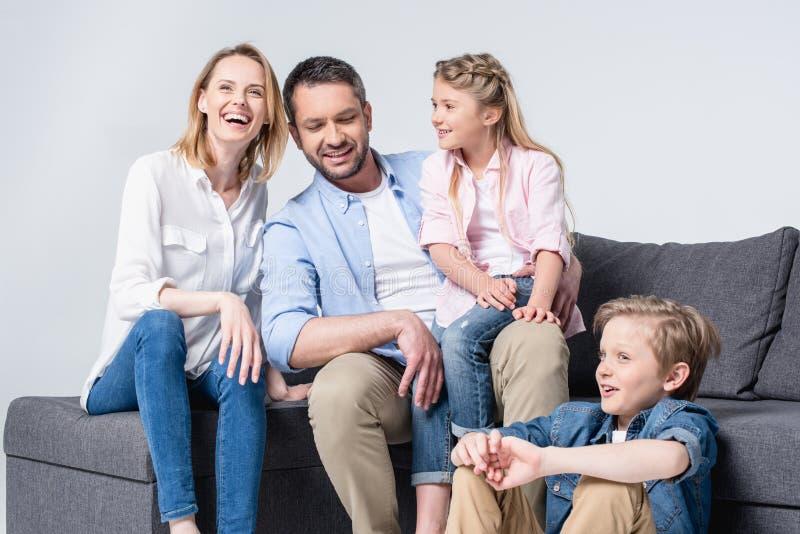 Giovane famiglia con due bambini che si siedono insieme sul sofà e sul sorridere fotografia stock libera da diritti