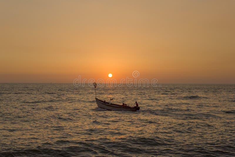 Giovane famiglia con i bambini in un grande battello da diporto con un motore nell'oceano contro il cielo giallo arancio luminoso immagine stock