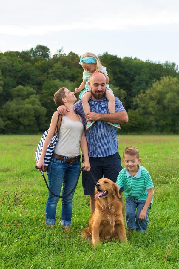 Giovane famiglia con il loro cane di animale domestico, golden retriever immagine stock libera da diritti