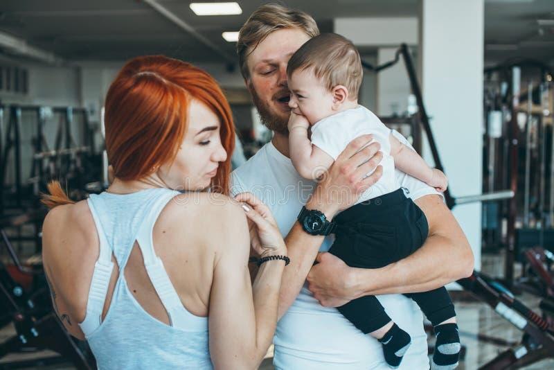 Giovane famiglia con il ragazzino nella palestra fotografia stock