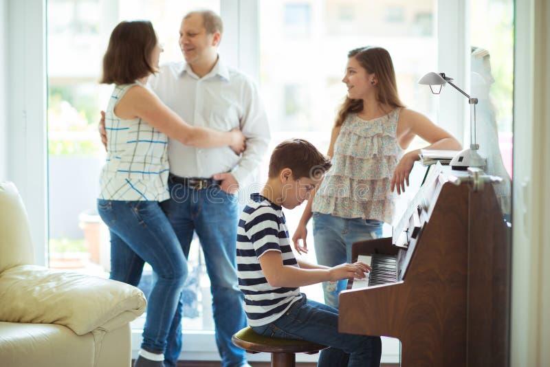 Giovane famiglia felice che ascolta come cildren la musica del piano dei giochi immagini stock libere da diritti