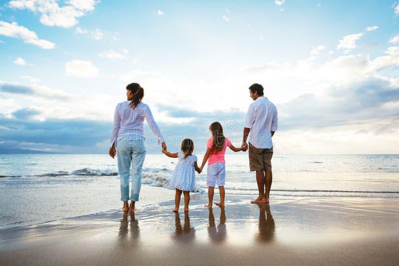 Giovane famiglia felice che cammina sulla spiaggia fotografia stock libera da diritti