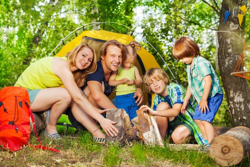 Giovane famiglia felice che fa il fuoco del campo nel legno immagine stock