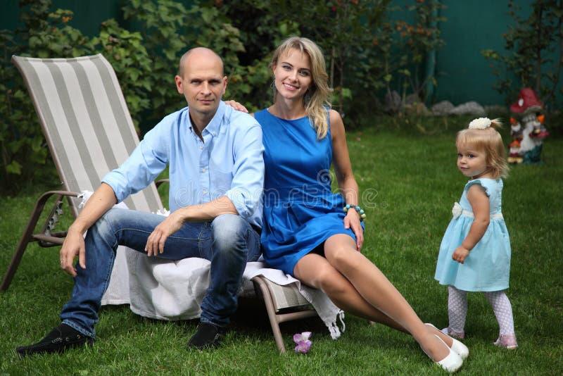 Giovane famiglia felice che gioca sull'erba Papà, mamma e piccola bella figlia Una giovane coppia che si siede sulle sedie a sdra fotografia stock