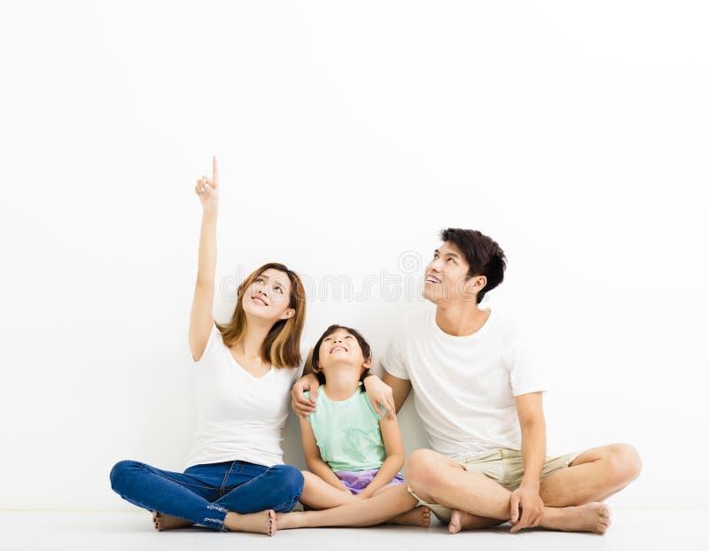 Giovane famiglia felice che indica e che cerca immagini stock libere da diritti