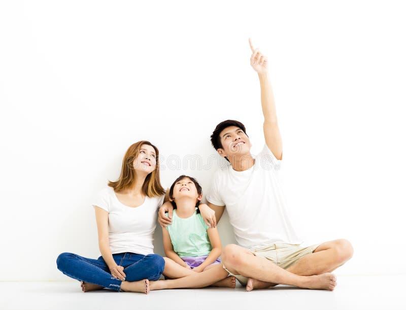 Giovane famiglia felice che indica e che cerca immagine stock libera da diritti